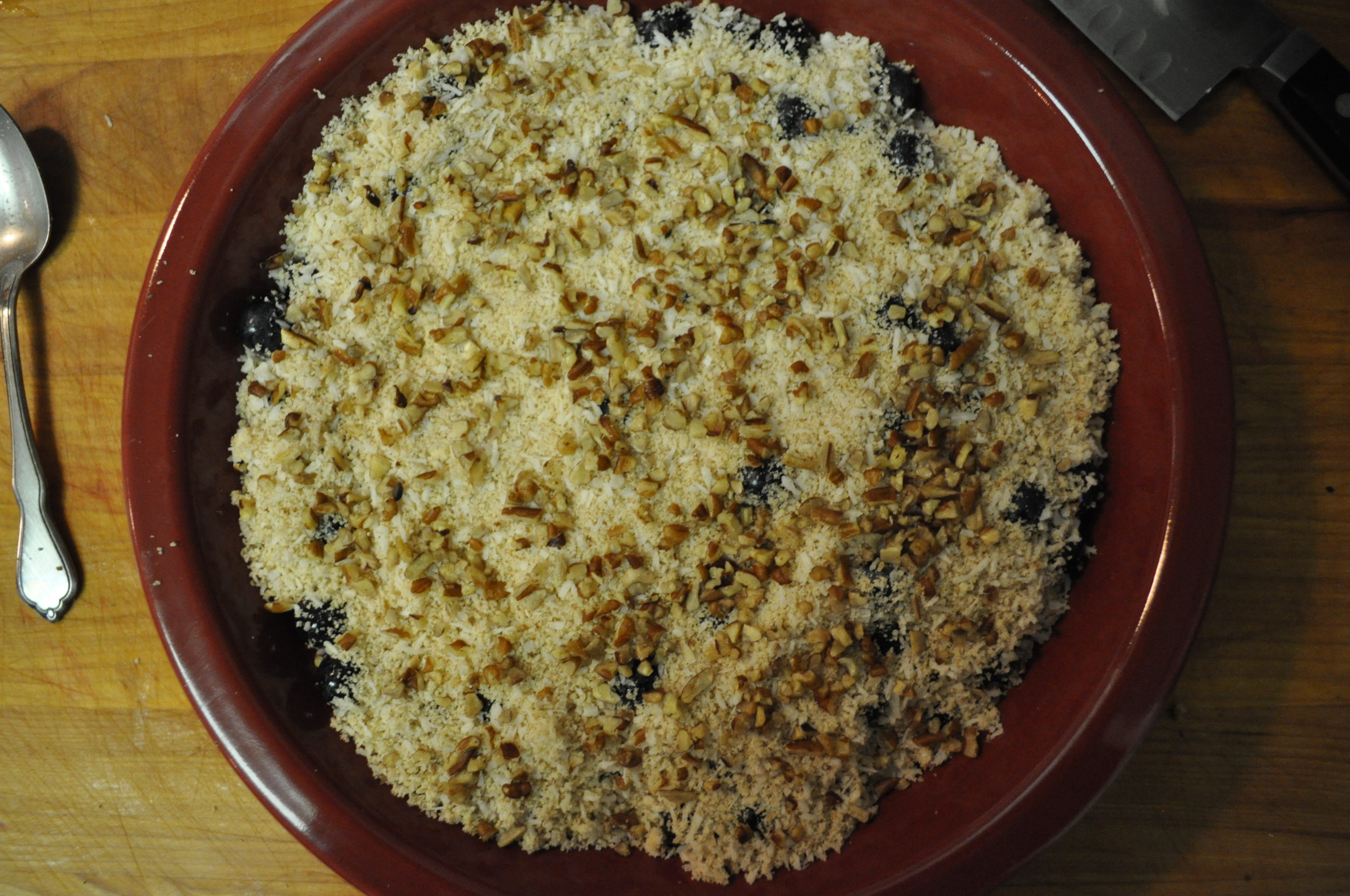 overhead view of a red casserole dish filled with blueberry coconut crumble
