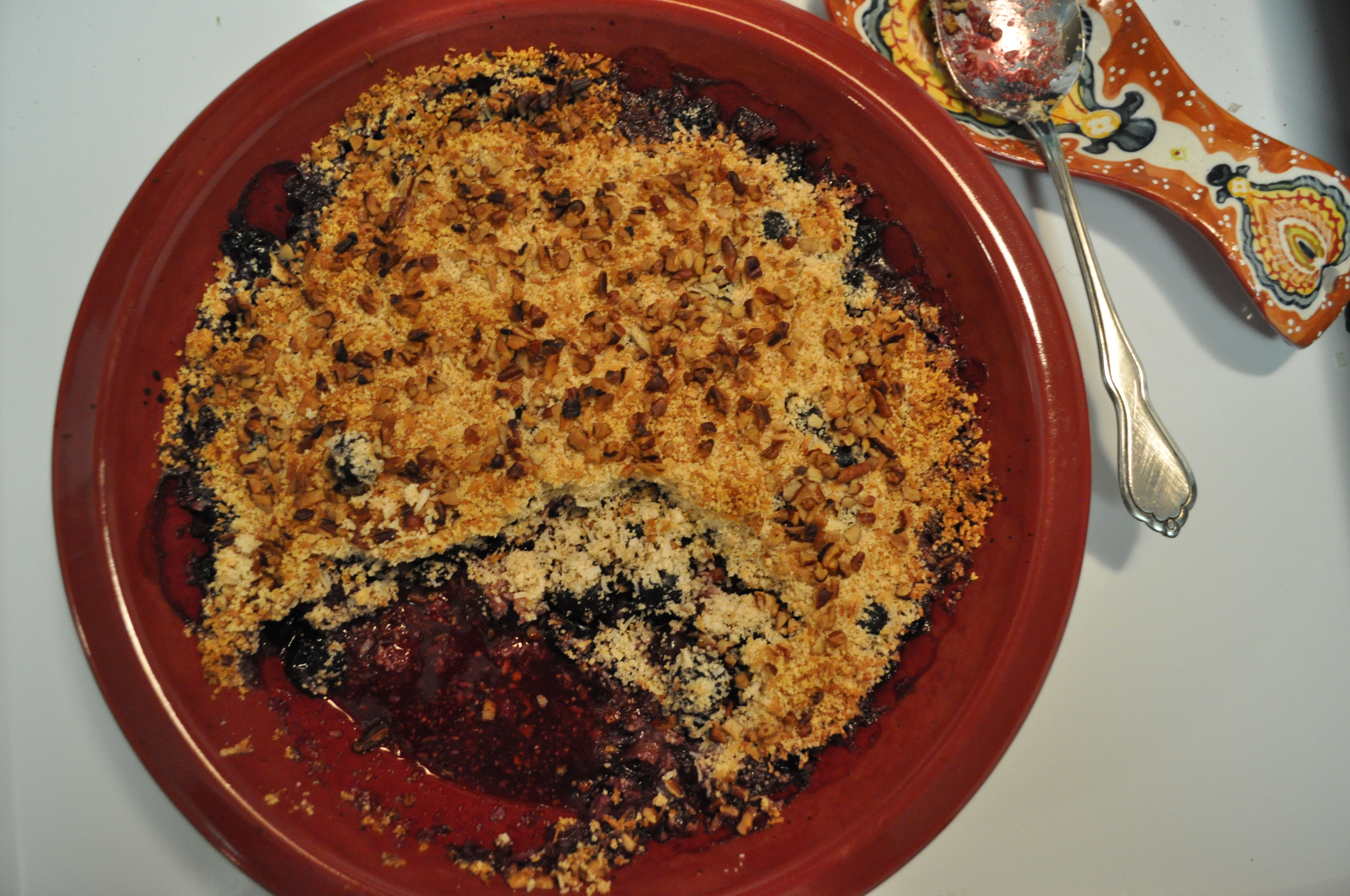 overhead view of a red casserole dish filled with baked blueberry coconut crumble